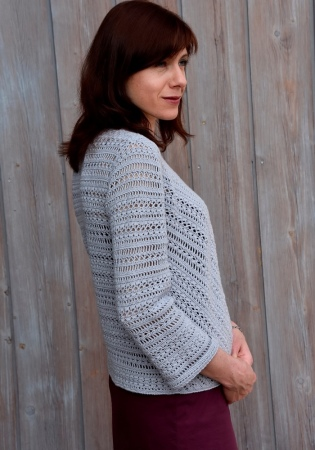 Crochet pattern for sizes XS-XL. Features diagonal patterns in front, three quarter sleeves and button at neckline.